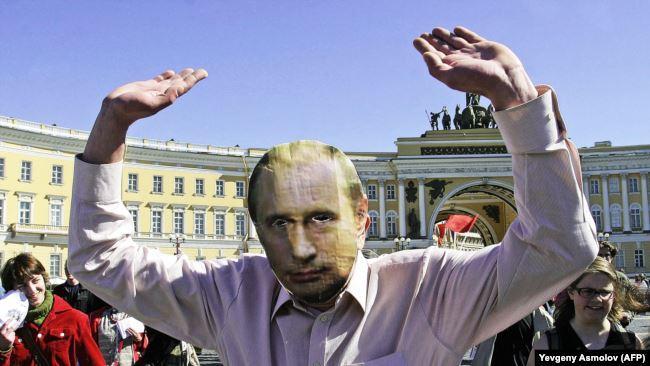 Человек в маске с изображением Владимира Путина