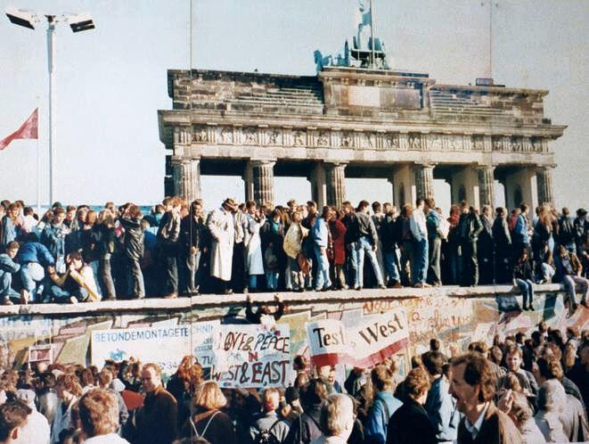 Стена с взобравшимися на неё немцами на фонеБранденбургских ворот. Фото: © Wikipedia