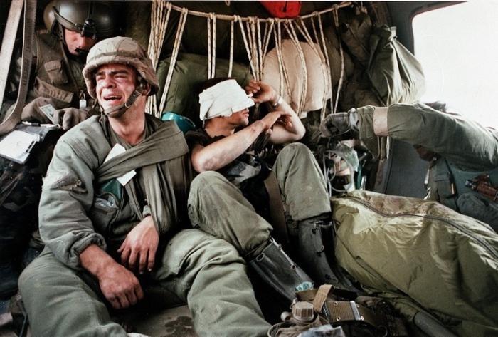 Раненый солдат плачет рядом с упакованным в мешок телом погибшего товарища.