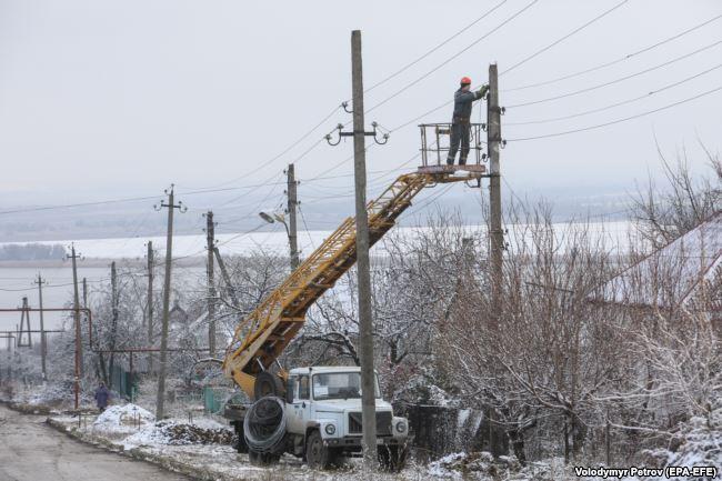 Рабочие восстанавливают линию электропередач в Новолуганском