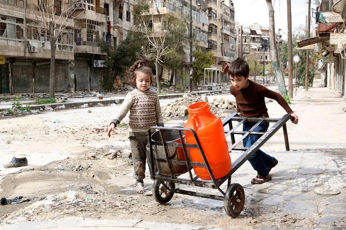 Поход за водой на разбомбленной улице в Алеппо, Сирия.