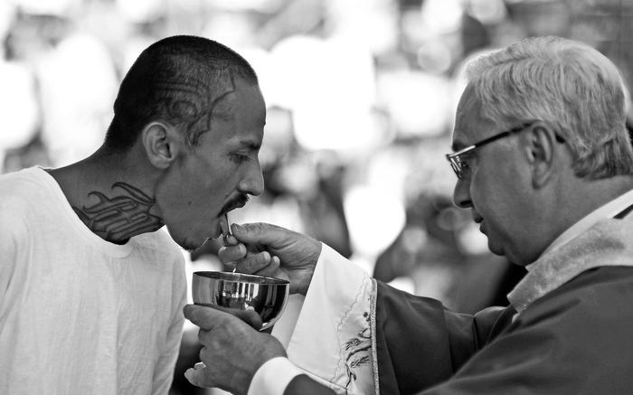 Член банды Mara Salvatrucha получает причастие от священника. Фото: © REUTERS/Ulises Rodriguez