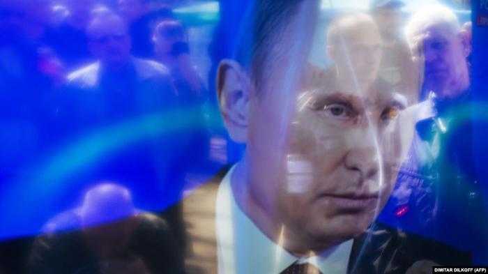 Зрители отражаются в экране во время телеобращения Владимира Путина